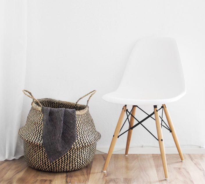 Silla blanca contra una pared blanca en un suelo de madera